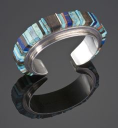 An early (circa 1960′s) inlayed bracelet by Charles Loloma.  Bracelet is inlayed with Kingman turquoise, ironwood, Mediterranean coral and lapis.  Measures 5 1/4″″ with a 1″ opening.  7/8″ width.