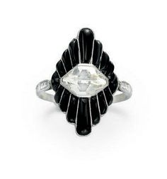 AN ART DECO DIAMOND AND ONYX RING   Centering upon a fancy old mine-cut diamond, within a scalloped navette-shaped black onyx surround, to the single-cut diamond shoulders, mounted in platinum, circa 1920