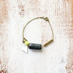 Chartreuse Grey Chain & Charm Bracelet / geometric mixed-media arm candy ft. porcelain, mother of pearl, brass triangles, faceted brass tube. $25.00, via Etsy.