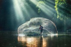 """Suloara Allokendek has a soft spot for fishermen and seems to always be ready at the right moment—when the shape of the net is full and majestic. He snapped this moment with a Canon 5D Mark II with a deep depth-of-field—probably zooming in from quite far away. The photo is called, simply, """"jala""""—the Indonesian word for """"net""""."""