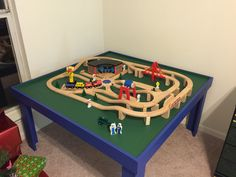 """Children's train table. Plywood top and pine legs and apron. Acrylic and """"chalkboard"""" paint. Train set by Melissa and Doug."""