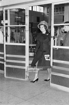 Princess Soraya Of Iran, Former Wife Of Shah Reza Pahlavi At Orly Airport. Paris, en octobre 1960. Résidant en Europe entre l'Italie, l'Espagne et la France depuis son divorce d'avec le Shah REZA PAHLAVI, prononcé le 14 mars 1958, la princesse SORAYA prend l'avion à l'aéroport d'Orly. Dans l'aéroport, entre deux portes vitrées, la princesse SORAYA, seule.