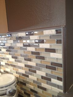 Glass mosaic backsplash in neutral colors, complete with Schluter edge  profile pieces.