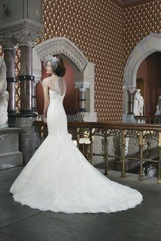 Свадебное платье со шлейфом силуэта «русалка» из шантильского кружева, прикрытого сверху алаксонским кружевом на прозрачной основе из тюльмарина.  Особенность этого платья – блистательное оформление области декольте.  Прозрачная накидка, закреплённая на лифе, украшена полосами ювелирного декора по вырезу, «ампирной» линии талии и краю цельнокроеного рукава.  Пуговицы, обтянутые королевским атласом, декорируют застёжку-молнию.  Кружевное свадебное платье 2014 года.