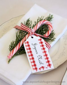 """DIY Christmas Place Setting: Take a plain napkin, cut a sprig of greenery from a pine tree, add a candy cane, and a Joyeux Noel Tag, and tie it up with some red and white striped ribbon ... A great idea from this blog, """"A Spoonful of Sugar""""."""