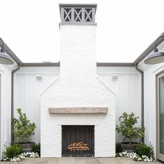 white stone fireplace with black herringbone tile insert, enclosed patio courtyard with fireplace