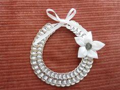 Collier en capsules de canettes avec une fleur blanche.