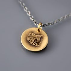 Tiny 14k gold and sterling silver ginkgo leaf necklace by Lisa Hopkins Design... Matches my tattoo :)
