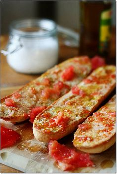 "Pa amb tomàquet. Literally in English: ""Bread with tomato"". It's a simple and typical recipe in Catalonia. It consists of bread — optionally toasted — with tomato rubbed over and seasoned with olive oil and salt. Sometimes garlic is rubbed on the bread before rubbing in the tomato."