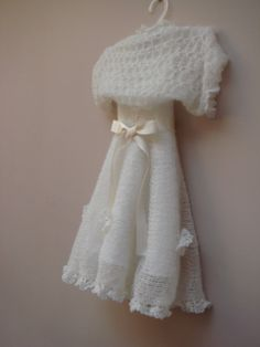 www.elegantboutique.co.uk It's hand knitted from white mohair, decorated with crochet flowers. The dress has fastening buttons at the back, it has got a satin underdress.  A little bolero- shrug comes with this dress.    It's a perfect gift for a baby girl, for her Christening or Birthday.