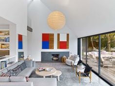 Will Meyer of Meyer Davis updated this 1971 modernist home by Hugh Newell Jacobsen in the Long Island hamlet of Springs as a vacation home for his family. In the living room, a pair of color-field works by Enrique Batista are mounted over the fireplace, and an Isamu Noguchi lantern hangs from the vaulted ceiling. Furniture includes Kaare Klint armchairs and a Milo Baughman barrel lounge.