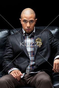 young criminal sitting on couch - Portrait of confident young gangster sitting on couch over dark background