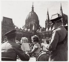 ROBERT CAPA 1948 [Girls watching musicians before Parliament in Lojos Kossuth Square, at the celebration of the 100th Anniversary of the Hungarian Army, Budapest, Hungary]