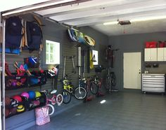 On-the-wall family storage. The best thing you can do to keep your garage organized is to get things off the floor. This garage makes use of a handy system that keeps everything from scooters to surfboards out of the way.
