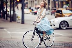 darya kamalova a fashion blogger from thecablook in dallas texas on the bycicle in polka dot shirt and blue skirt with gold espadrilles and other storie bag for rewardstyle rsthecon