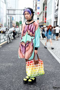 Yana is a 22-year-old guy who is seen often around Harajuku. In addition to his purple hairstyle, his look here features an oversized W.I.A. graphic top, neon socks, and YRU platform sandals. Accessories include a devil horns beret, a leather o-ring choker, MYOB earrings, and a Jeremy Scott x Longchamp keyboard print handbag. (Tokyo Fashion, 2014)