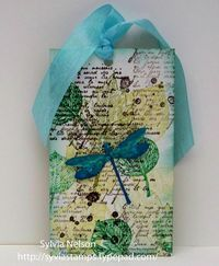 Dragonfly tag in green, yellow and aqua tones.