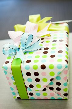 Cute gift boxes wrapped in colorful polka dot wrapping paper and tied with girly ribbons.