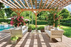 Friends and family enjoy poolside relaxation beneath Legacy Homes' pergola outfitted with furnishings from Janus et Cie set to maximize the enjoyment of the outdoor spaces.