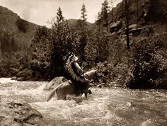 You are looking at an artistic picture of Bullchief Ford a Crow Warrior.  It was created in 1905 by Edward S. Curtis.The picture presents Bullchief wearing his warbonnet, crossing a shallow rapids on horseback. This is a dramatic presentation of an authentic Native American.
