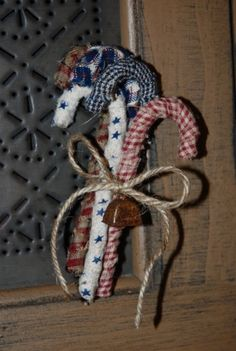 Fabric wrapped candy canes: fabric scraps, plastic candy canes, glue gun, mini bells and rope or ribbon. All items on hand or from the Dollar Store