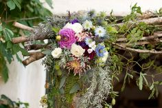 The couple wed under a trellis overflowing with a rustic display of blooms.