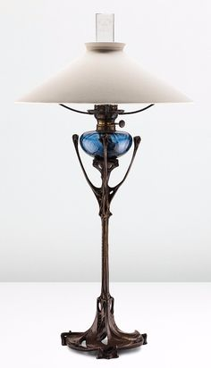 HECTOR GUIMARD Rare table lamp, from the Maison Coilliot, Lille, circa 1900,patinated bronze, colored blown glass, clear glass chimney, painted brass, brass, fabric shade, 38 3/4 in. | SOLD $80,500 Phillips New York, Dec. 16, 2014