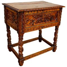 This side table is an example of Spanish Colonial Revival. It displays ornate plant carvings on the front and sides and spindle carved legs. The single drawer has two iron pulls.