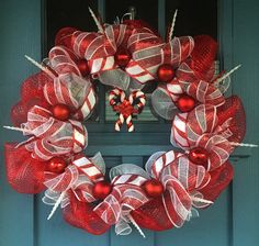 """- Wire wreath frame covered with red and white mesh intertwined with """"candy…"""