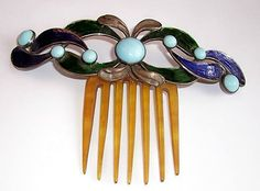 The metal tiara is hinged to a horn comb, painted with dark blue and green enamel, and decorated with turquoise cabochons in this Art Nouveau comb. c. 1900.