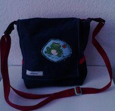 Diese Schultertasche ist eine besondere Kreation, da die Tasche auf der Rückseite (!) mit Steckschnalle verschlossen wird.  Die Außenseite ist aus Jeansstoff und ist mit einer Applikation verziert, die aus dem Stoff gearbeitet wurde, den ich auch für das Futter der Tasche verarbeitet habe. Die Innenseite ist aus einem unifarbenen Stoff (rot)und aus einem Motivstoff (mit Fröschen) gearbeitet. Innen kann man seine Kleinigkeiten in einer Tasche verstauen.