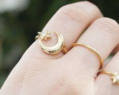 anillo con banda curvada del ct 9 placa de oro amarillo bebé daisy.  Usado en la imagen 3 con nuestros anillos de nido de bebé, disponibles aquí: http://etsy.me/2cDrkyo   ct 9 amarillo placa de oro sobre plata de ley (. 925) Daisy mide 5mm (h) x 6mm (w) Cubic zirconia piedras Tamaños disponibles (tamaño británico del anillo): tamaño de tamaño L, tamaño P, T. Incluye caja de regalo lista- Se vende como un solo anillo   Plateamos toda nuestra propia joyería para asegurarse de que...