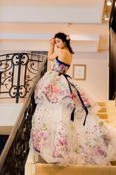 THE HANY リリアン  ホワイト地にネイビーのラインとヴィヴィットなボタニカ柄を組み合わせた図案は、ヨーロッパの名立たるコレクションを手掛けているイタリアのアトリエで製作されました。  プリントを全面使いした2段ティアードスカートをチュールのバルーンスカートで覆うことで奥行きが出て柄に立体感が生まれます。  されにバラ柄のラメ刺繍を所々に施すことで輝きをプラスし、ピオニーなど7種類の花をバルーンの中と外にに飾り付けて、立体感と華やかさを演出します。  THE HANYはNIKO名古屋店にての取り扱いとなります。  ご試着ご希望のお客様は下記の商品番号をスタッフにお申しけ下さい。  商品番号:リリアン