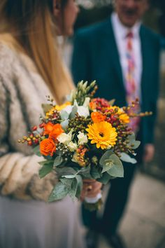 Bride in Ghost Dress, Fur Jacket & Autumnal Bouquet - Story + Colour Photography | Two Part Wedding with Humanist Ceremony at The Worx London | Gold Wedding Dress | Forest Green Ghost Bridesmaid Dresses | Autumnal Flowers | Geometric Terrarium Decor