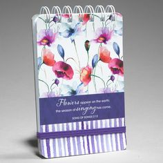 """Wirebound Notepad Seeds Of Love  Songs 2:12  You'll love the watercolor florals and pretty stripes on our Seeds of Love Gift Collection, expressing the love of God through inspiring Scripture quotes and soft touch feminine designs.  Wirebound notebook with elastic band closure and 80 lined pages. 4"""" x 6"""".  Flowers appear on the earth, the season of singing has come. Song of Songs 2:12.  PRICE: R50 per Notebook."""