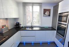 High gloss acrylic white U shaped kitchen in handleless style and with decorative blue LED plinth lighting.