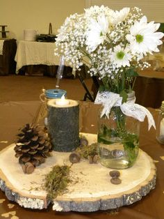 our center pieces....Log/wood disc...mason jar with lace ribbon and daisys....acore caps,pine cone, moss, Log tea light holder