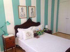 Quarto de visitas vintage, com móveis e detalhes cheios de história. A parede é pintada, em listras de 30cm.