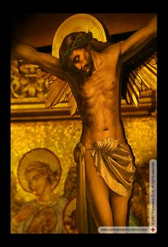 Christ on the cross. This beautiful artifact is placed in a space behind the altar, which walls are covered with golden mosaics (visible in the background). Saint Sophia Greek Orthodox Cathedral, Los Angeles.