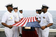 Sailors prepare a flag for a burial at sea aboard USS Dwight D. Eisenhower by Official U.S. Navy Imagery, via Flickr