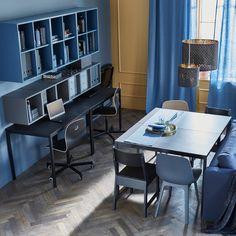 In un soggiorno, due tavoli uniti uno di fronte all'altro formano un ampio tavolo da pranzo; altri due, addossati alla parete, fungono da scrivania - IKEA