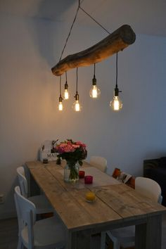 Wooden tree trunk lamp and dinner table                              …