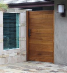 Modern style architecture is in right now and this wooden entry/courtyard gate completes this house in Newport Beach, CA. With the wood laid horizontal and the nondescript hardware this door compliments the contemporary features of this house.