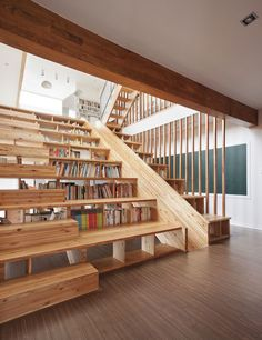 South Korean house by Seoul studio Moon Hoon, where a wooden slide is slotted into a combined staircase and bookshelf