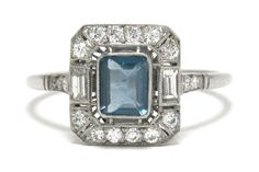 The Santa Monica Art Deco aquamarine engagement ring. Like floating in a pool, a vivid, deep, sky-blue emerald cut gemstone is held within in a dainty milgrain bezel with an interesting baguette diamond halo is inspiring. #engagementring #love #artdeco #ido #engagementrings #artdecoring #artdecorings #aqua #aquamarine #aquamarinering #aquamarinerings #skyblue #blue #haloring #halorings #targetring #targetrings #bridalring #bridalrings #engaged Art Deco Ring, Art Deco Diamond, Halo Diamond, Estate Engagement Ring, Antique Engagement Rings, Aquamarine Rings, Baguette Diamond, Bridal Rings, Emerald Cut