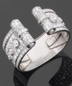 An Art Deco platinum and diamond cuff, by Ostertag, circa 1930. The cuff with geometric motifs set with diamonds, the ends terminating with two scrolls. Signed. #Ostertag #ArtDeco #cuff #bangle