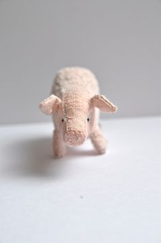 Little Being designed and handmade by Alice.Patricia the Pig (a very noble swine) is sewn out of a pink german viscose.  She is weighted with steel shoot for complete authenticity!Her nose and mouth are hand sewn, stitched into a contented smile and she has japanese black bead eyes.Her cheeks a tinted a blush pink and her coat has beem trimmed and sculpted.- AW seal of authenticity on back trotter.Height: 4.5cm  Length:8cm