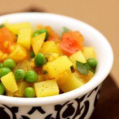 Baktijd aardappels: 10 min Bereidingstijd: 10 minVerhit de olie tot ze heet is en voeg dan gember en look toe. Bak gedurende 30 seconden. Voeg ui, zout en aardappels toe en bak tot de ui zacht en goudbruin is. Roer regelmatig. Voeg het kerriepoeder en de tomaten toe. Kook tot de meeste vloeistof verdwenen is en het mengsel een dikke brij vormt. Blijf roeren. Voeg de erwtjes en de groentebouillon toe en breng aan de kook. Zet het vuur zachter en laat sudderen tot de aardappels gaar zijn…