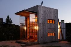 Sustainable holiday hut in Whangapoua, New Zealand - by Crosson Clarke Carnachan Architects.  The two-story awning winches open to form an awning and reveal the large steel doors, which open the hut up completely to the outside.