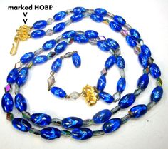 HOBE Gorgeous 2 Strand AB w Cobalt Blue Foil Glass Necklace, Aurora Borealis Diamond Glass Rainbow Beads, Adjustable, Gold Logo Catch Gorgeous luminescent cobalt blue foil beads and rainbow AB luster diamond shaped glass beads, exciting color against the bright gold catch gather ends The necklace has an adjustable bead chain and fits from 18 to 20 1/2 ( 45.72cm to 52.07cm ) bottom strand hangs don 1 3/4 from the top ( 4.445cm)  Immaculate gift worthy no chips or cracks  LOOKS Mint Condition…